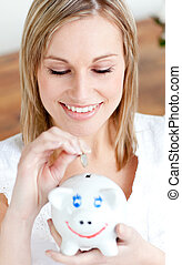 Delighted woman saving money in a piggy-bank