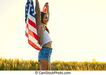 Delighted woman standing at sunset field with hands up, holding American national flag