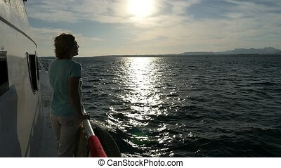 Delighted woman standing on ship`s bow and looking at...