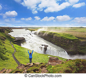 Delighted woman tourist on the shore of the waterfall. Gyullfoss