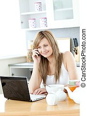 Delighted woman using a laptop in the kitchen