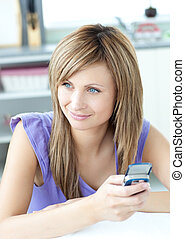 Delighted woman using a phone in the kitchen