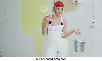 Delighted woman with brush and paint bucket - Happy smiling...