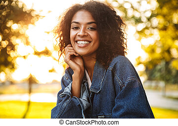 Delighted young african girl in denim jacket