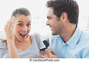 Delighted young couple getting engaged on the sofa
