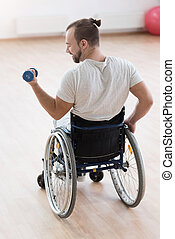 Delighted young disabled man exercising with weights in the gym