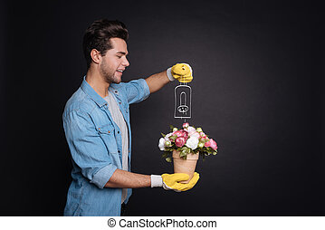 Delighted young man watering flowers.