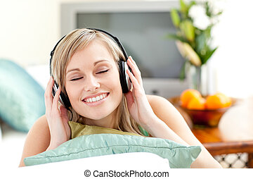 Delighted young woman listening music lying on a sofa -...