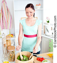 Delighted young woman preparing salad at home