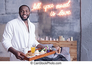Delightful African American man holding breakfast tray in the bedroom