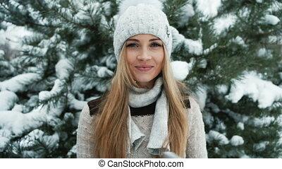 Delightful blonde smiles against background of snow-covered landscape.