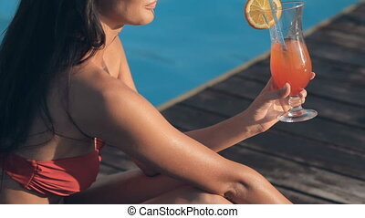 Delightful girl wearing a pink bikini sitting by the pool with a cocktail
