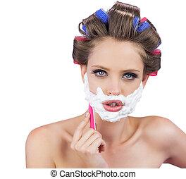 Delightful model in hair curlers posing with razor