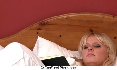 Delightful woman reading a book - Delightful woman lying on...