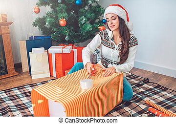Delightful young woman sits on floor and cuts tape with scissors on present box. She is concentrated but positive. There are presents and Christmas tree behind her.