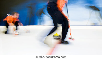Delivering a curling stone - Two players of a curling team ...