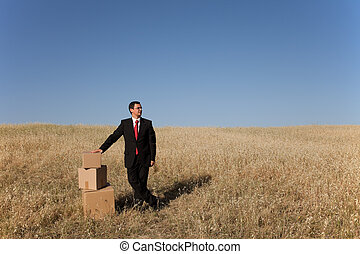 businessman with a stack of boxes at the field