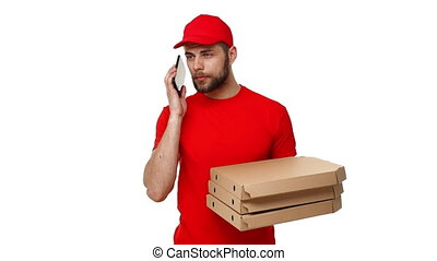 Delivery boy in a red uniform holding a stack of pizza boxes and checking order on mobile phone. Isolated over white background.
