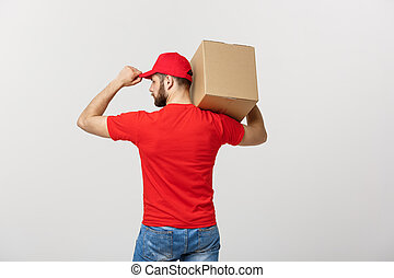 Delivery Concept - back view of Handsome Caucasian delivery man with box package. Isolated on Grey studio Background. Copy Space.