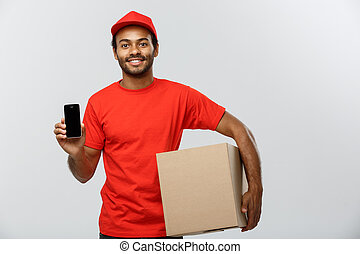 Delivery Concept - Portrait of Handsome African American delivery man or courier with box showing mobile phone on you to check the order. Isolated on Grey studio Background. Copy Space.