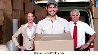 Delivery driver and business team smiling at camera in a...