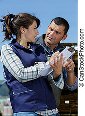 delivery driver and female manager outside a warehouse