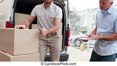 Delivery driver checking his list on clipboard with manager...
