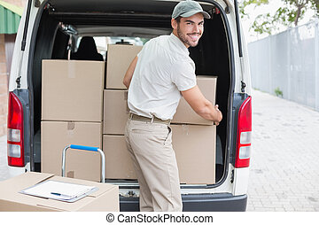 Delivery driver loading his van with boxes outside the ...