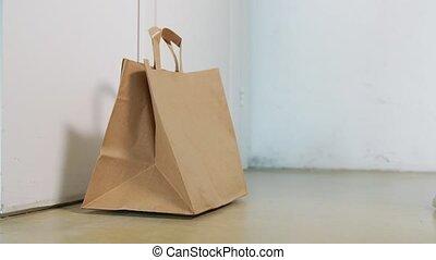 delivery girl in gloves leaving paper bag at door - health ...