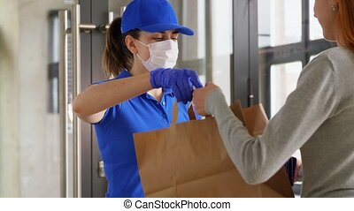delivery girl in mask giving paper bag to woman - health ...