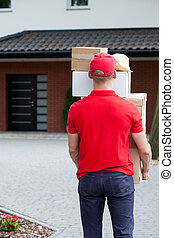 Delivery guy carrying package stack
