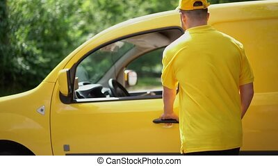 Delivery guy in yellow uniform gives parcel to female customer near car