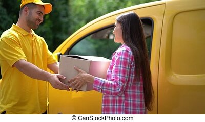 Delivery guy in yellow uniform gives parcel to female...