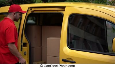 Delivery guy take out the package from yellow car - Man In...