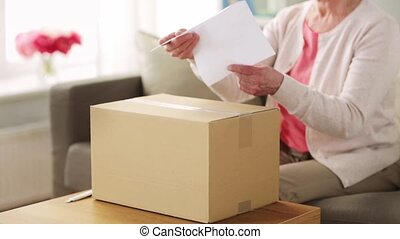 happy senior woman opening parcel box at home - delivery,...