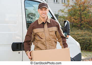 Delivery Man Carrying Cardboard Box With Truck In Background