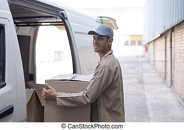 Delivery man carrying cardboard boxes outside the warehouse