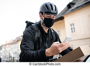 Delivery man courier with face mask and smartphone delivering in town.