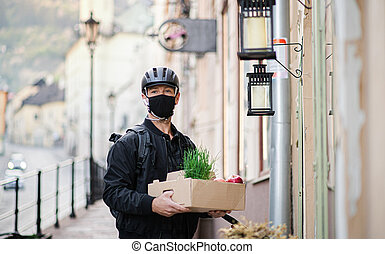 Delivery man courier with face mask delivering groceries in town.