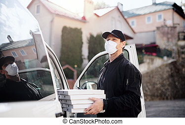 Delivery man courier with face mask delivering pizza in town.