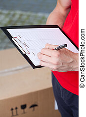 Delivery man filling in transport document
