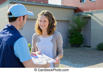 Delivery man handing over a registered letter - View of a...