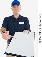 Delivery man holding out clipboard for signature