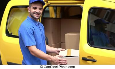Delivery man in blue uniform holds carton box near yellow...