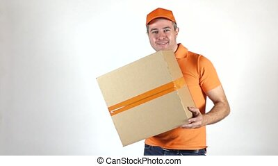 Delivery man in orange uniform throwing a big parcel at the camera. Light gray backround, slow motion studio shot
