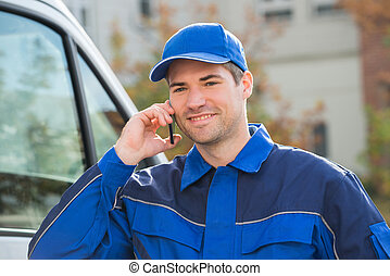 Delivery Man In Uniform Using Mobile Phone