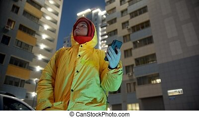 Delivery man in yellow clothes holding his phone and trying ...