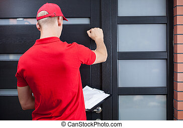Delivery man knocking on the client's door - Back view of a ...