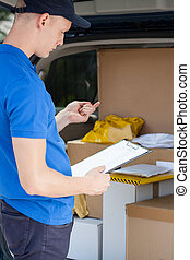 Delivery man looking at clipboard