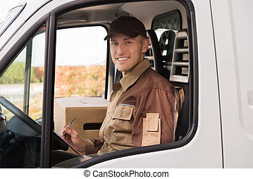 Delivery Man Making Checklist In Truck